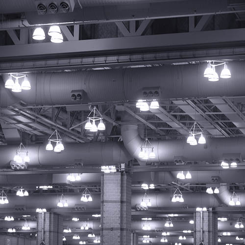 Overhead commercial lights fixtures with mercury vapor discharge lamps hanging from the ceiling of a large industrial building